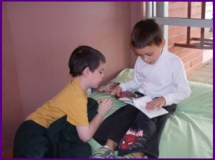 Two kids read a book