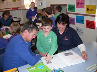 People from community groups help kids learning in the school