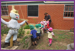 Kids and teacher together look after the vegetable garden